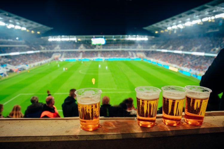 Fire fulle ølglass på en idrettsarena illustrerer Idrettsforbundets retningslinjer for alkohol