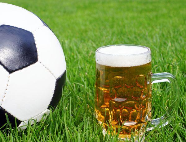 Fotball og ølglass på gressbane illustrerer Idrettsforbundets retningslinjer for alkohol