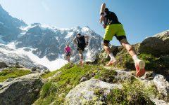 Ultraløpere på fjellsti. Snøkledde fjell i bakgrunnen