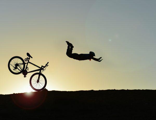 Syklist som stuper over styret etter at framhjulet støter mot en stein