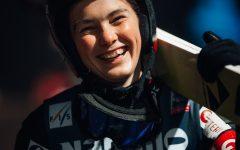Kvinnelig skihopper med hoppskia over skulderen
